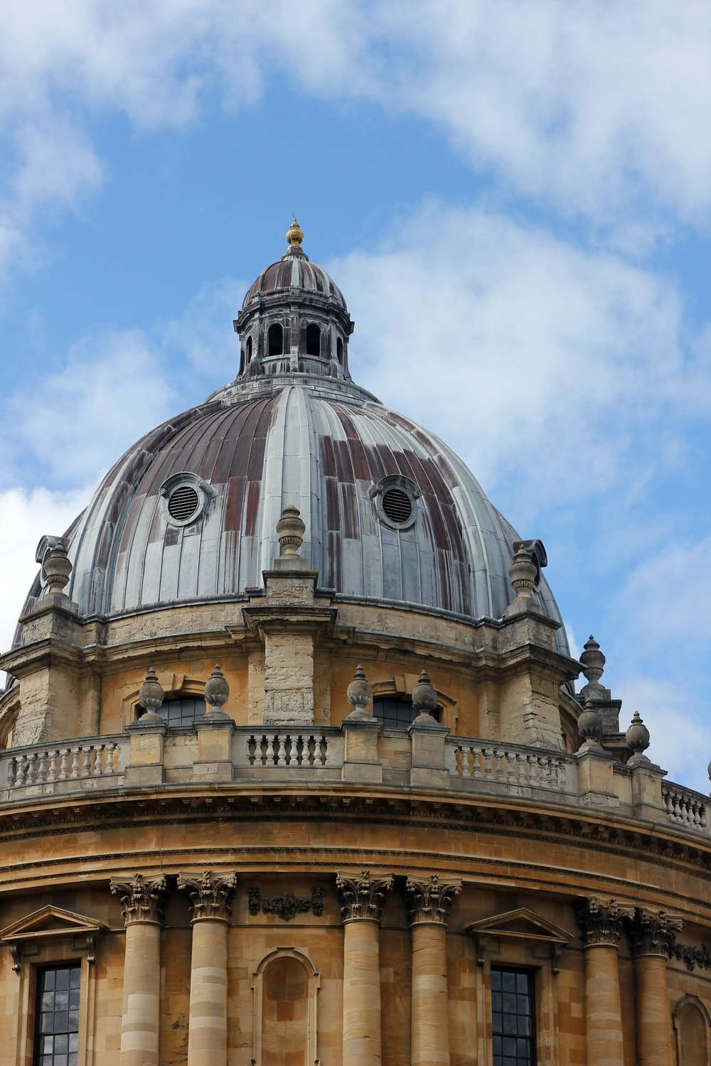 brown and gray dome building under white clouds and blue sky
