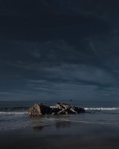rocks beside ocean during daytime