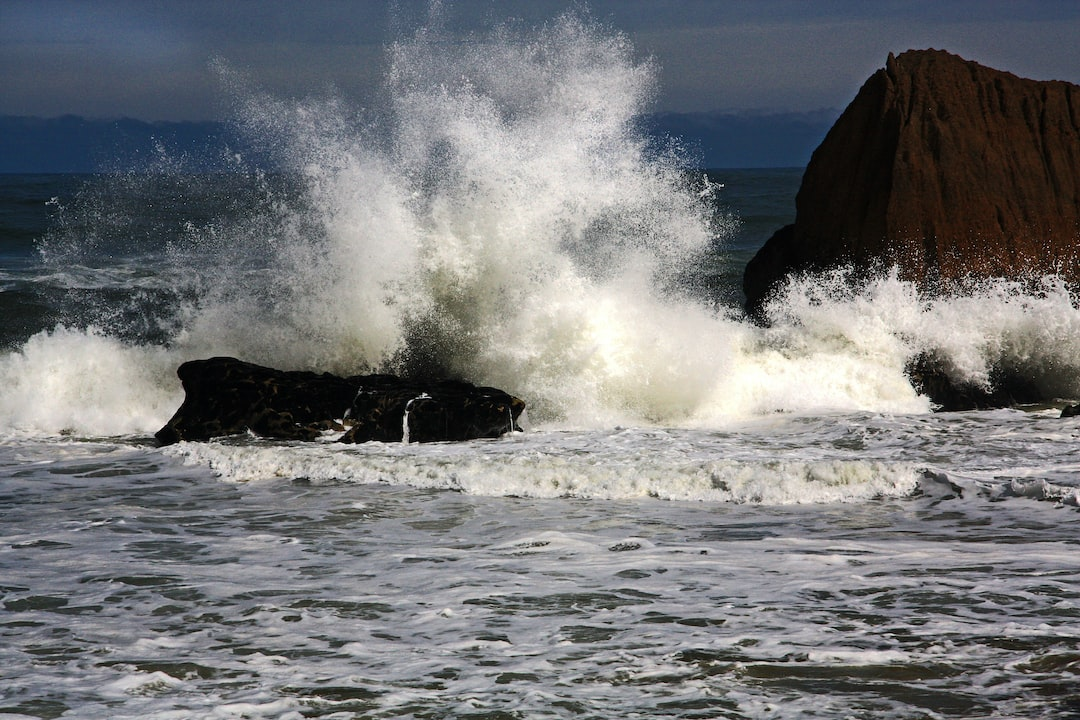 Spray and foam is tossed high in the air when a wave smashes into a rock as the tide comes in.