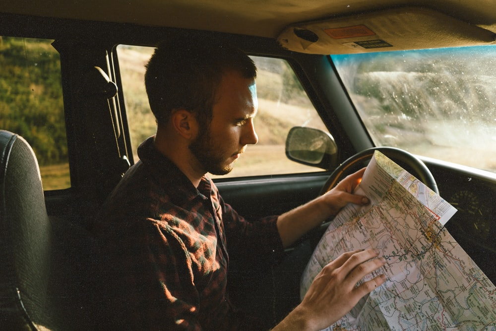 man riding on vehicle looking for map