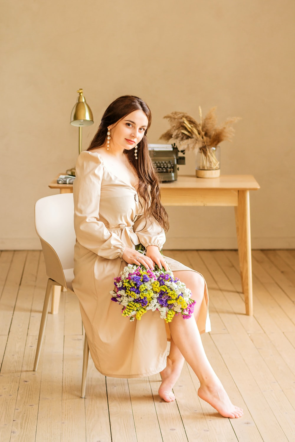 barefooted woman wearing white long-sleeved dress sitting on chair near rectangular beige wooden table