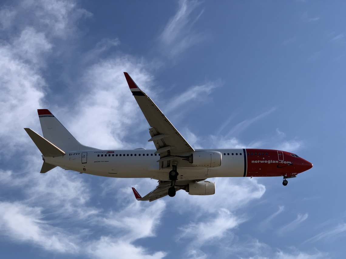 white and red airplane under blue and white skies
