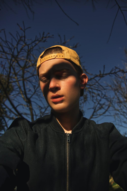 man wearing black zip-up jacket and brown hat