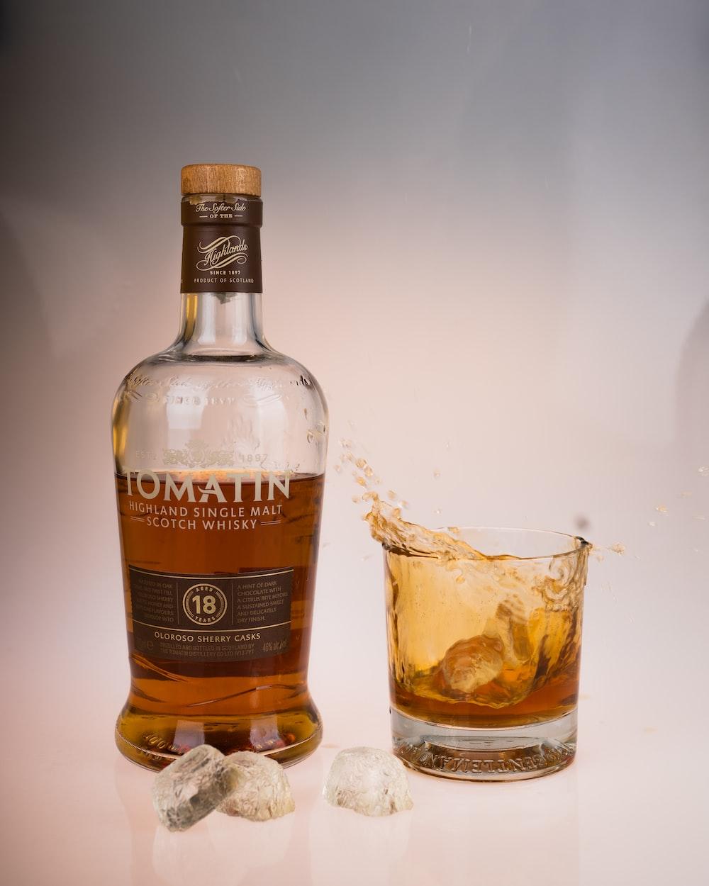 full clear glass beside Tomatin whisky bottle