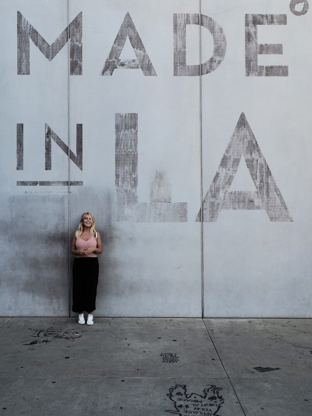 woman standing against wall with made in LA mark