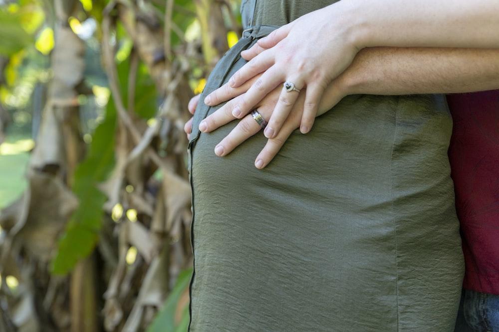 man wraps his arms around pregnant woman tummy
