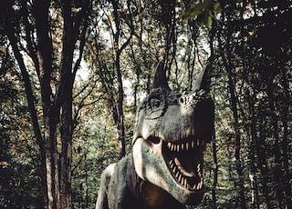 brown dinosaur beside tree
