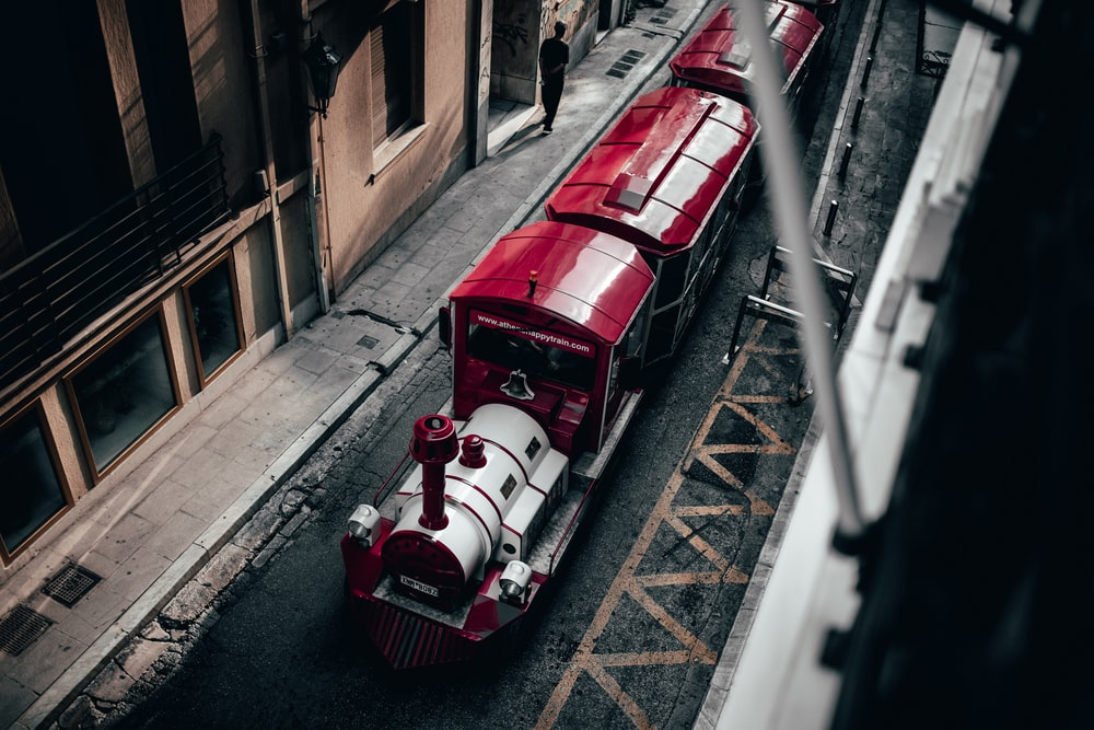 red and white train on road near buildings