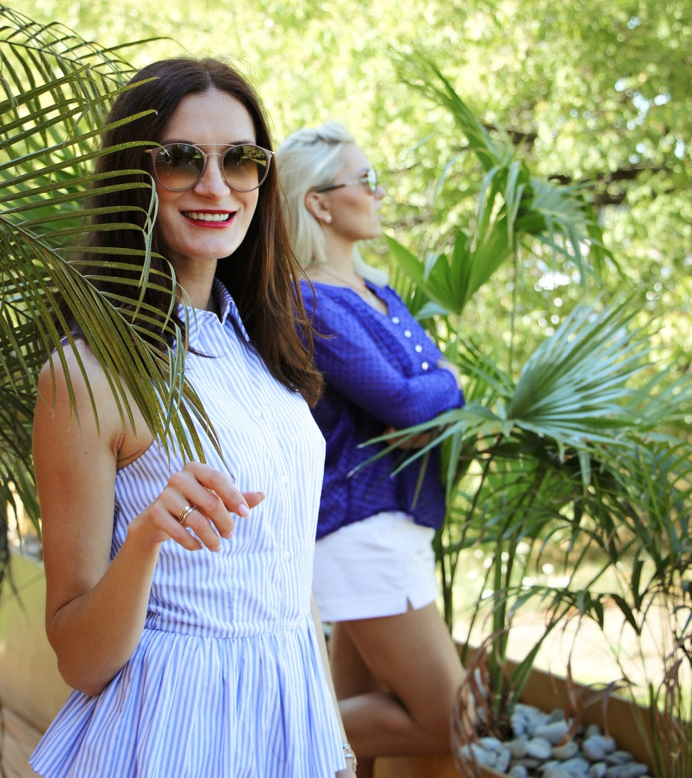 woman in white and blue pinstriped top standing outdoors