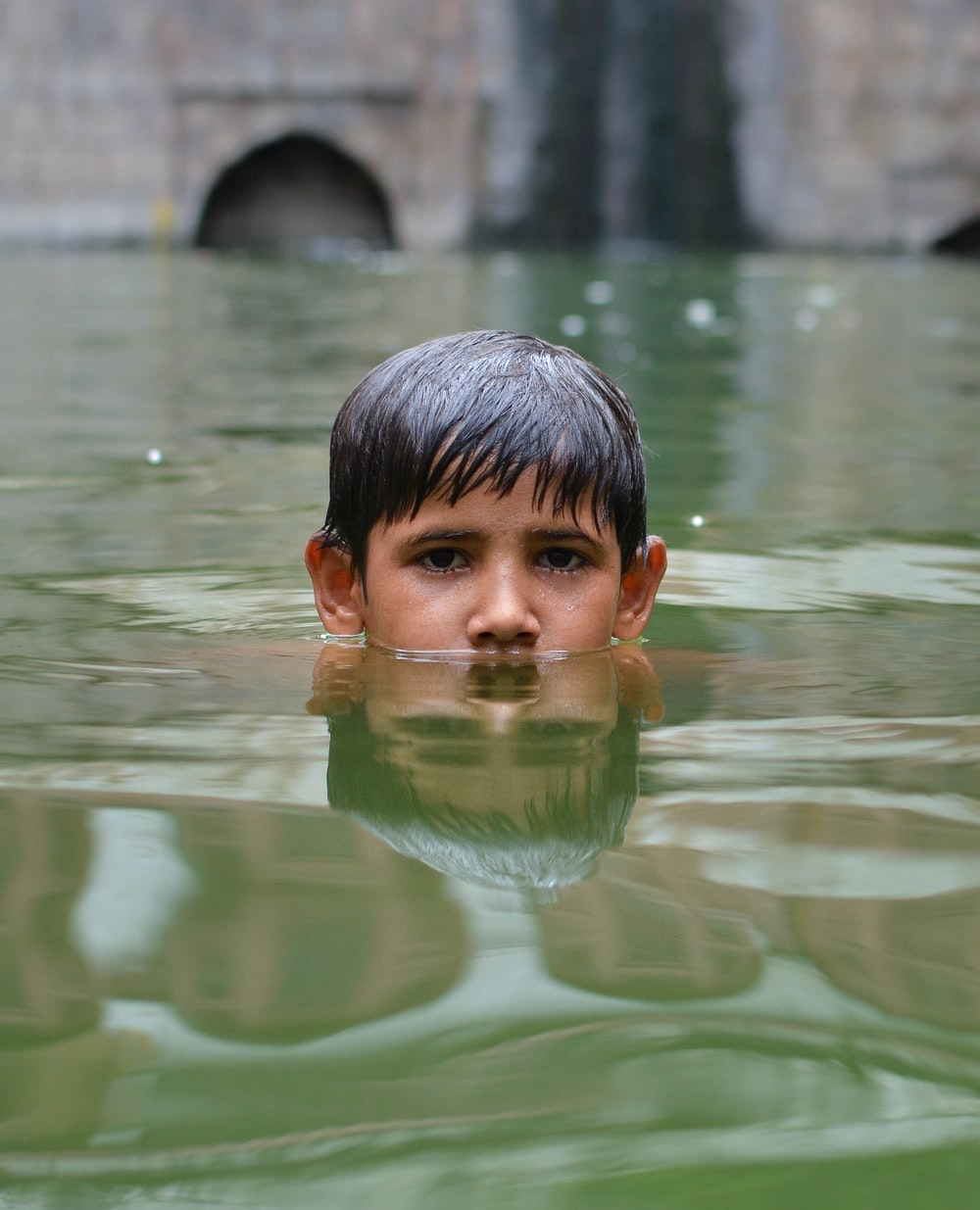 boy swims in body of water
