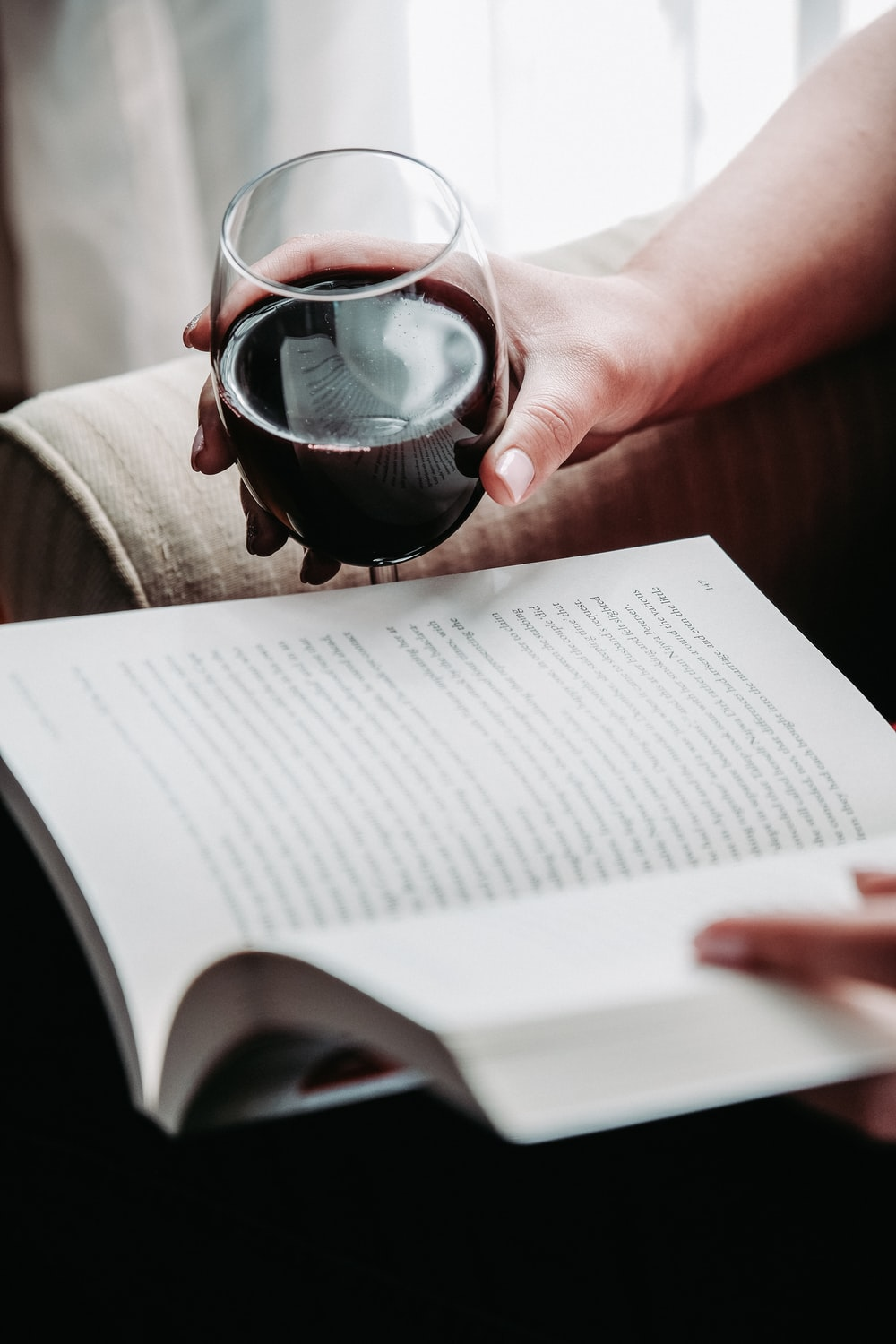 person holding goblet glass while holding book and reading