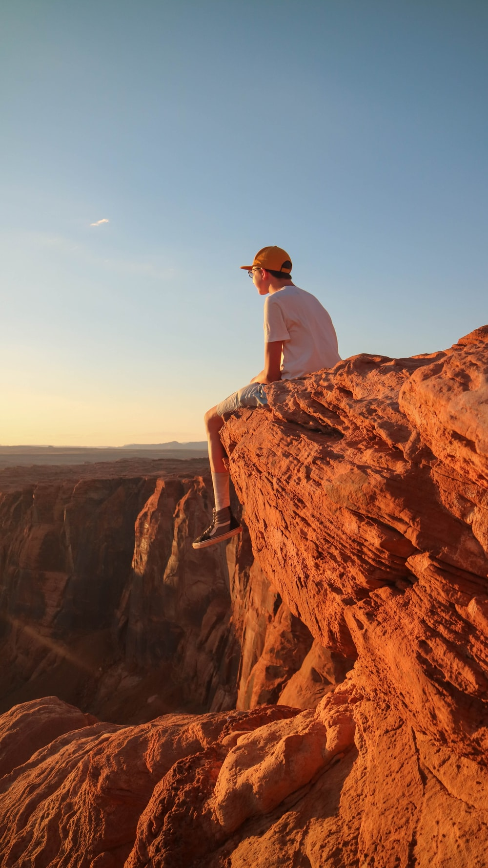 man in white top sitting on cliff