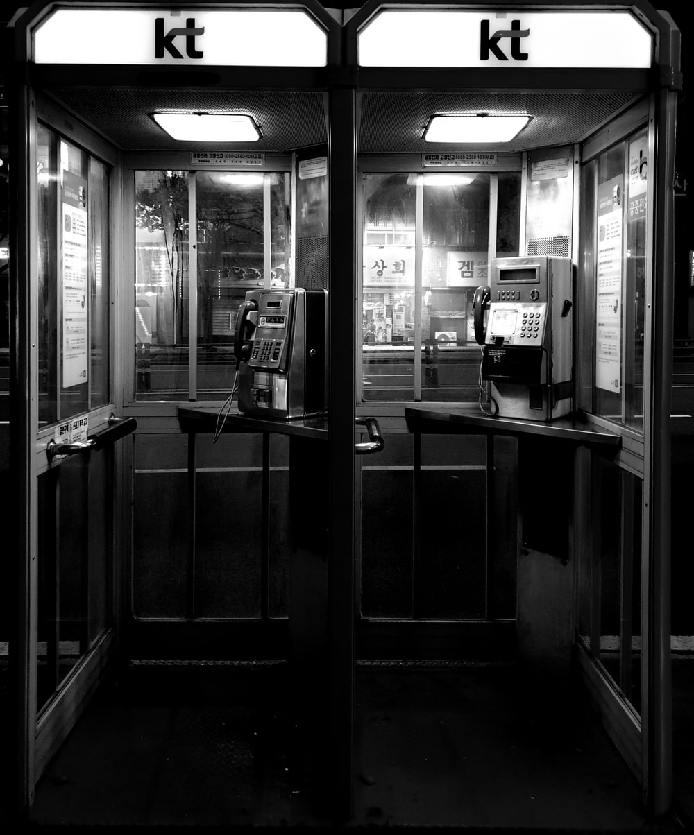 grayscale photo of payphone