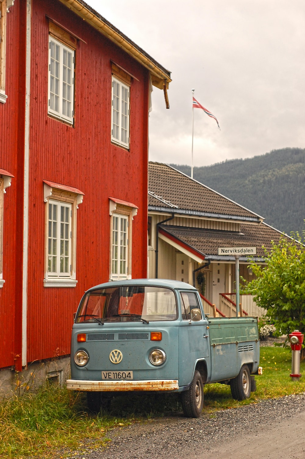 blue Volkswagen truck parked beside red structure