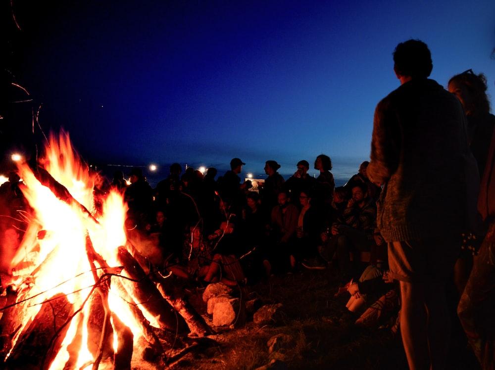 people gather near bonfire during night