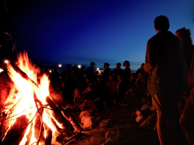 people gather near bonfire during night flame zoom background