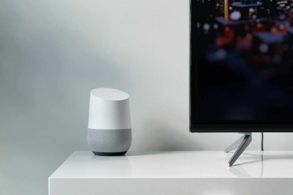 white and gray Google smart speaker beside black flat screen TV