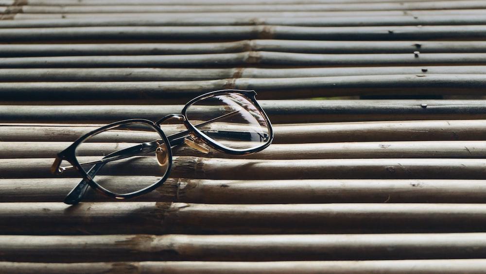 black-framed eyeglasses on wooden surface