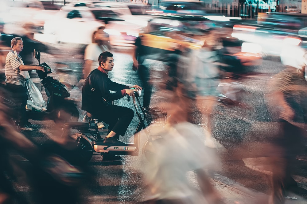 man riding scooter time lapse photo