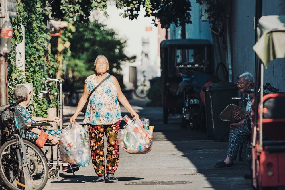 woman carrying two plastic bags of plastic bottles