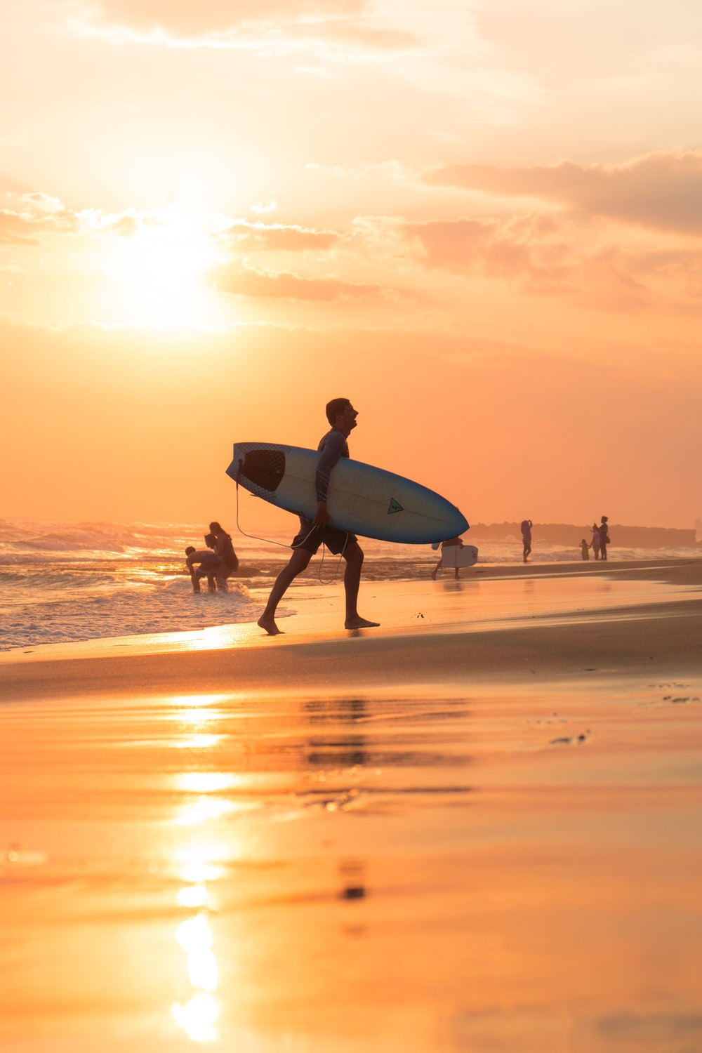 man holding surfing board during sunset