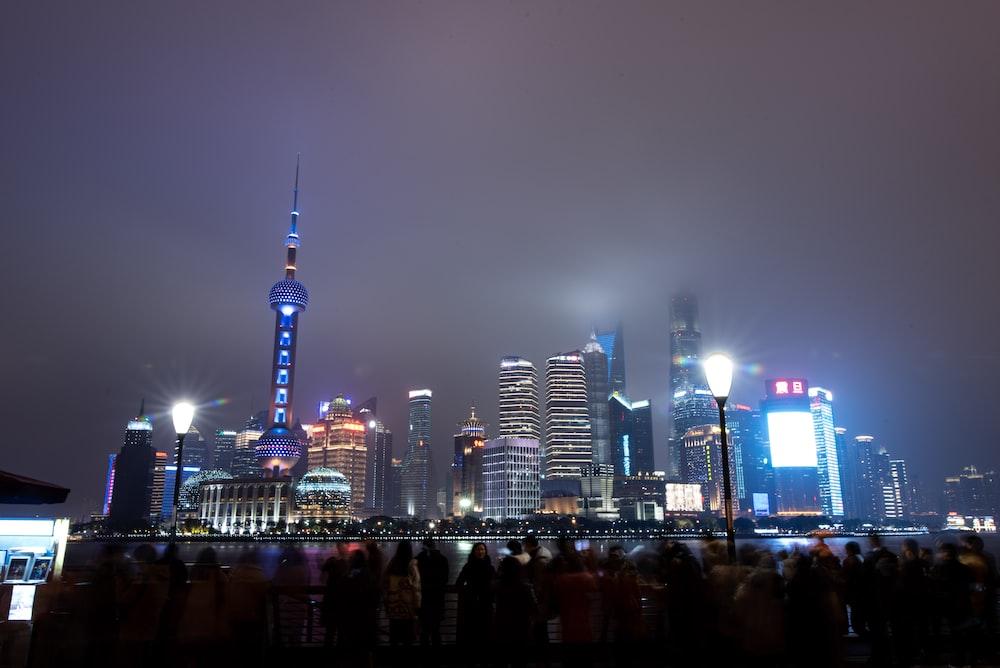 people facing buildings in Shanghai at night