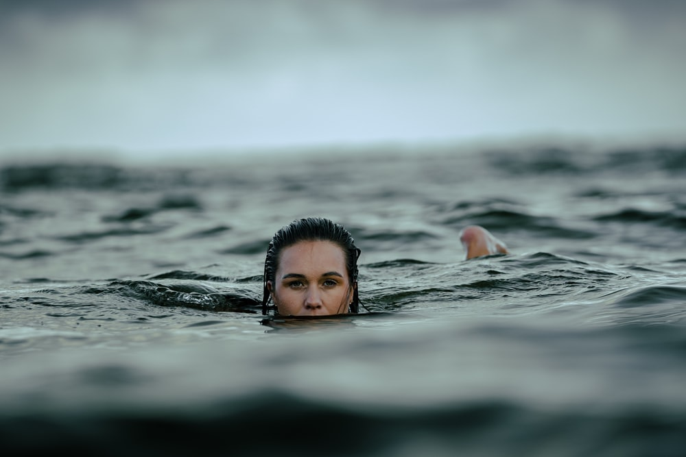 woman dipping in ocean