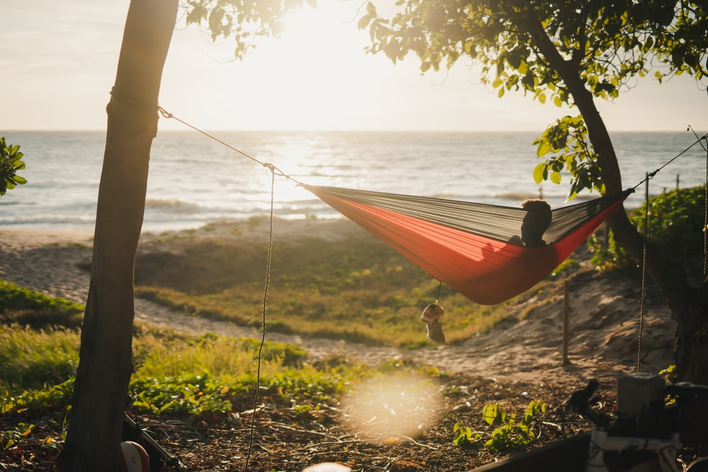 man on red and black hammock