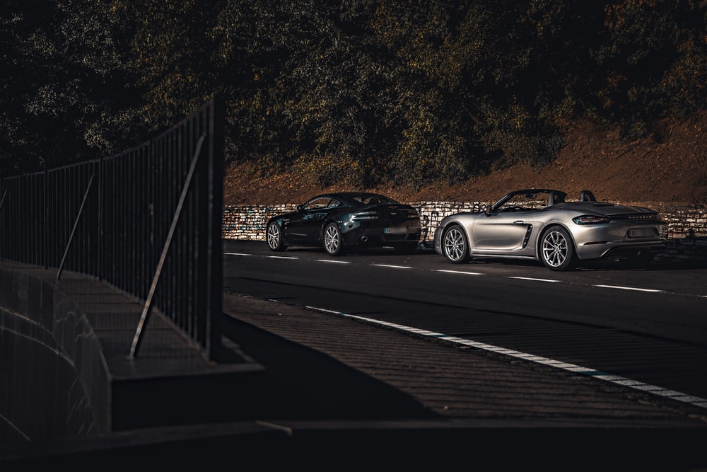 two silver convertible couple and black coupe on road during daytime