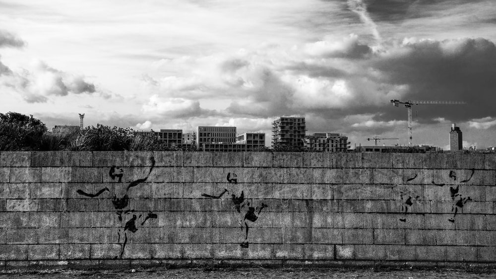 grayscale photo of concrete brick wall