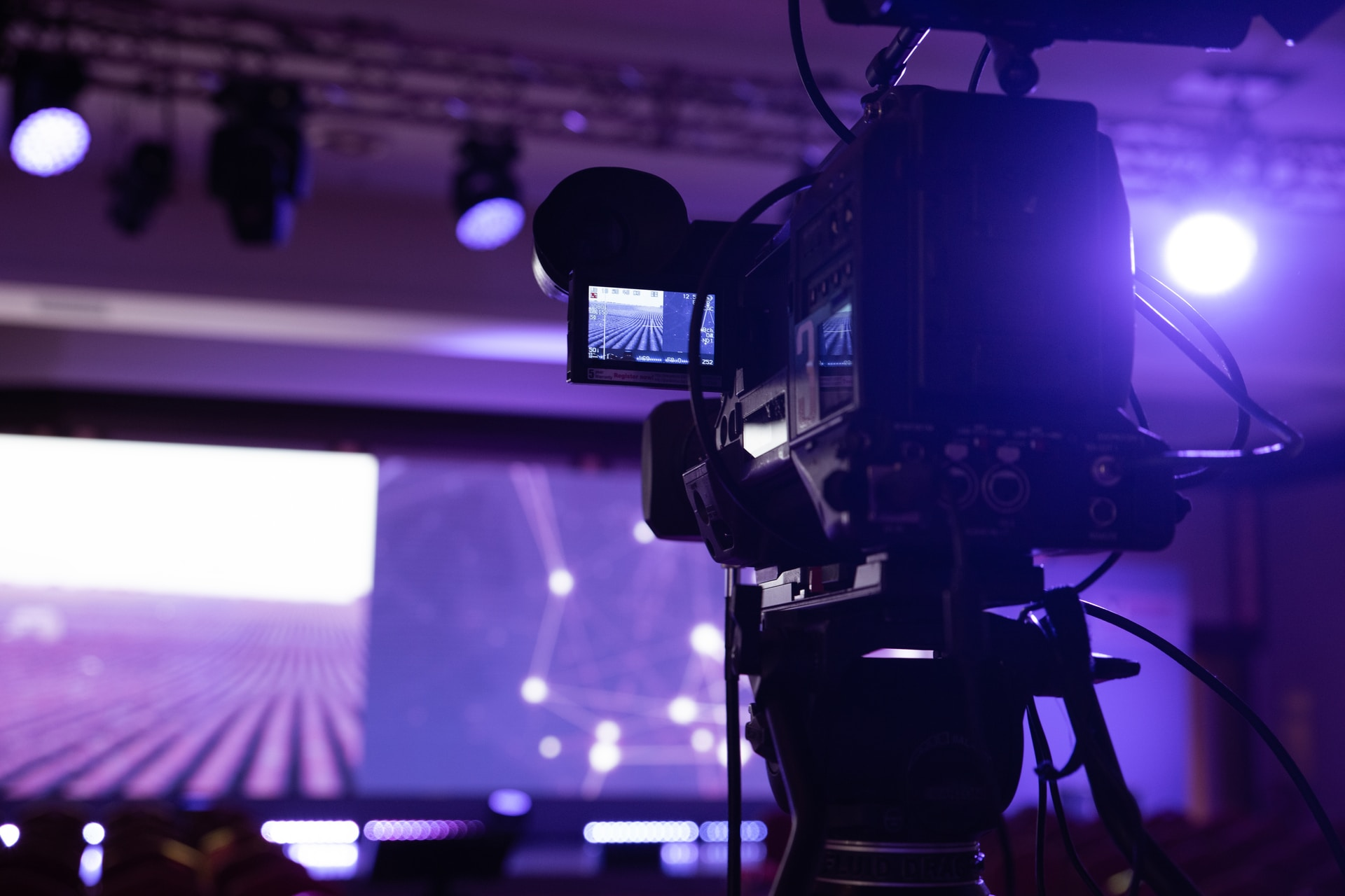 black video camera with tripod capturing stage