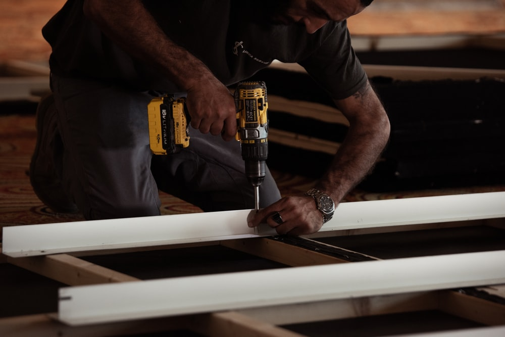 man drilling on a wooden plank using a power drill