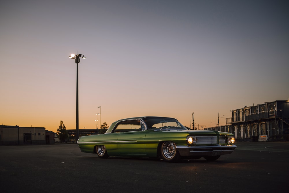 green coupe on road