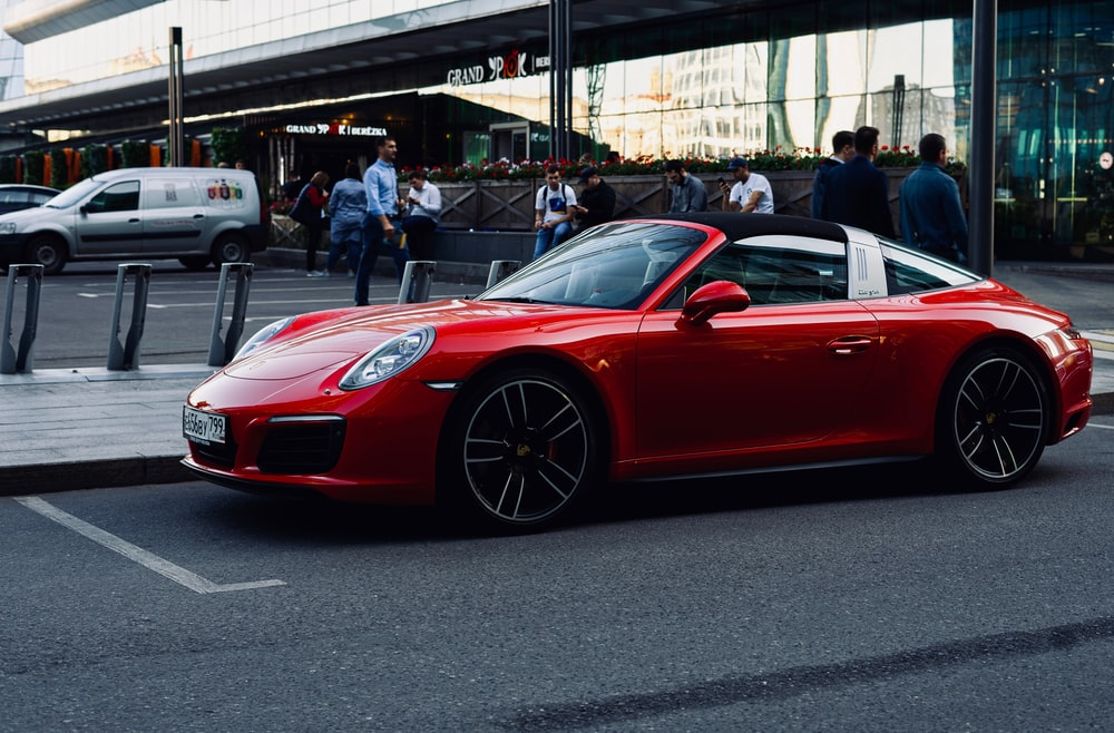 red convertible coupe on paved road