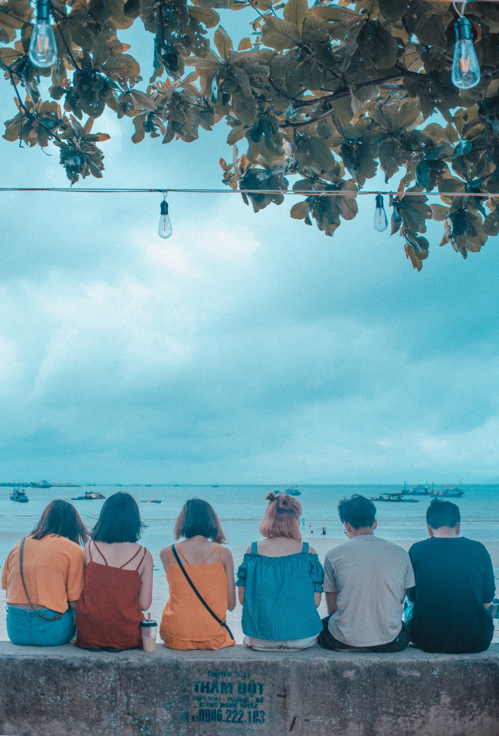 six people sitting and facing near blue sea under blue and white skies during daytime
