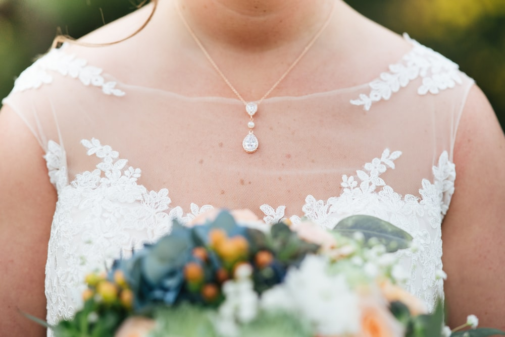 selective focus photography of woman wearing wedding dress holding bouquet