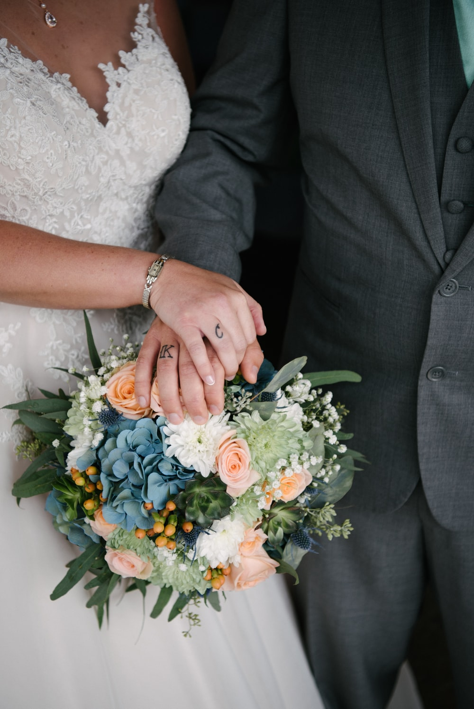 woman holding bouquet of flowers beside man touching it
