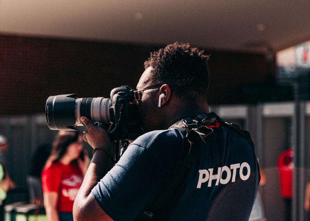 man wearing black shirt taking photo using DSLR camera