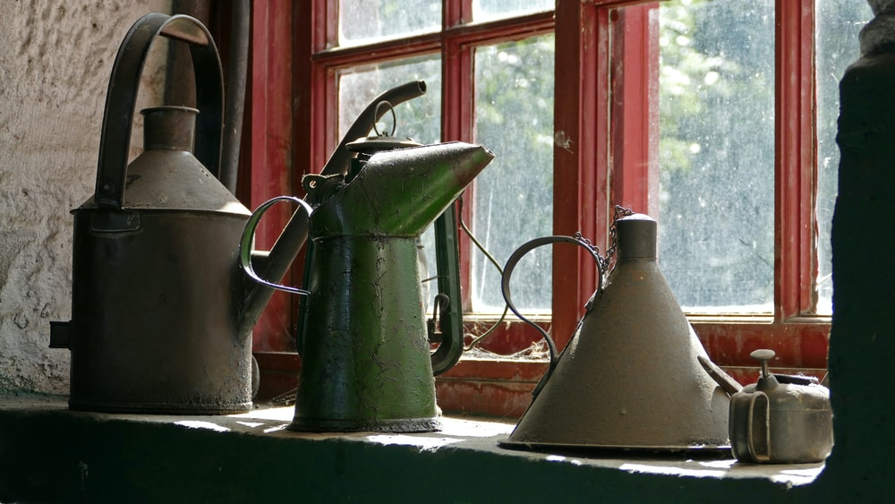 vintage four watering cans by window during daytime
