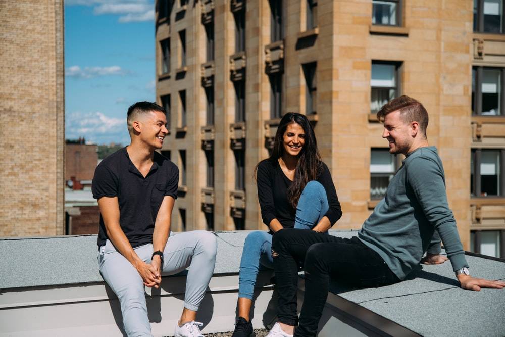 woman sitting between two men in a building rooftop