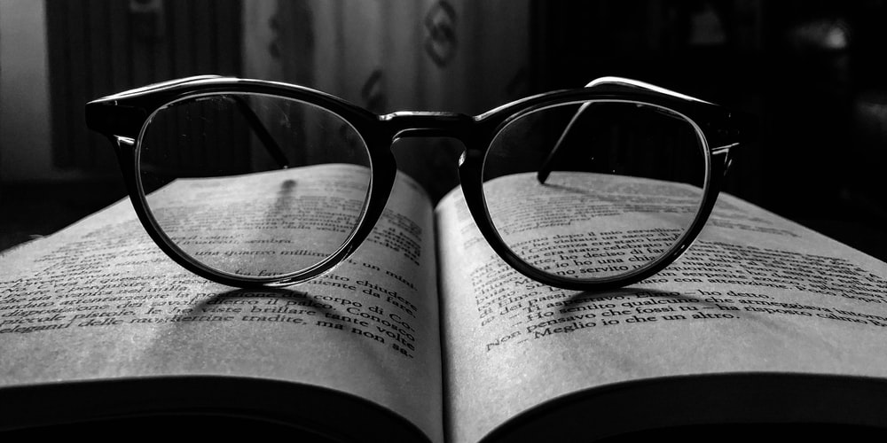 black frame eyeglasses on book