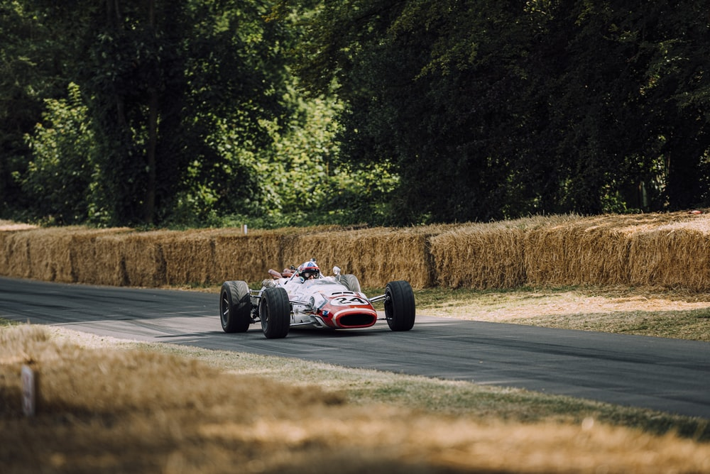 person riding racing car on road