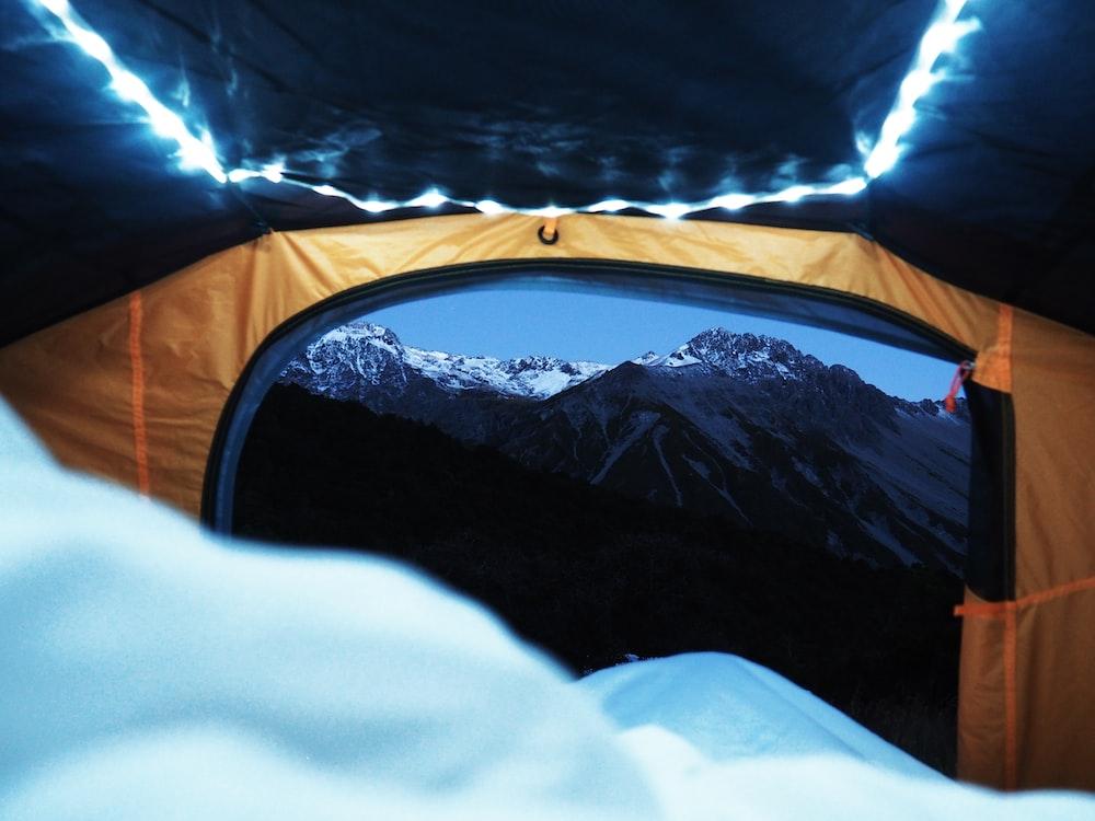 orange and black tent near mountains