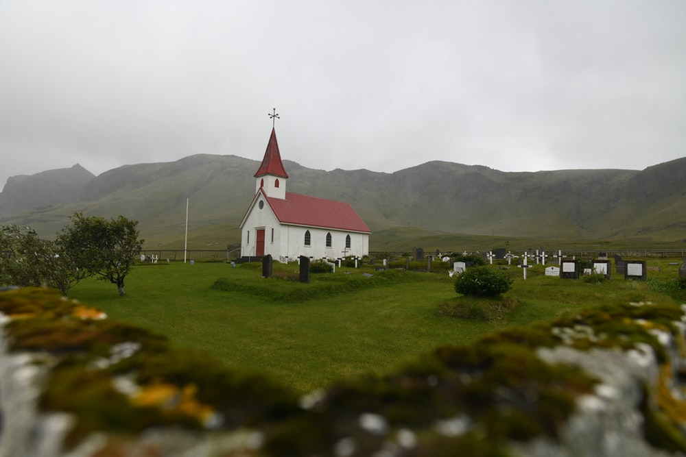 white and red chapel near grass field