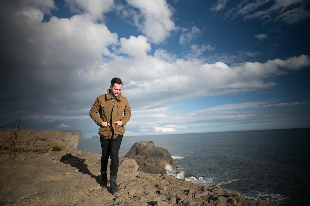 man walking on a mountain cliff overlooking the sea