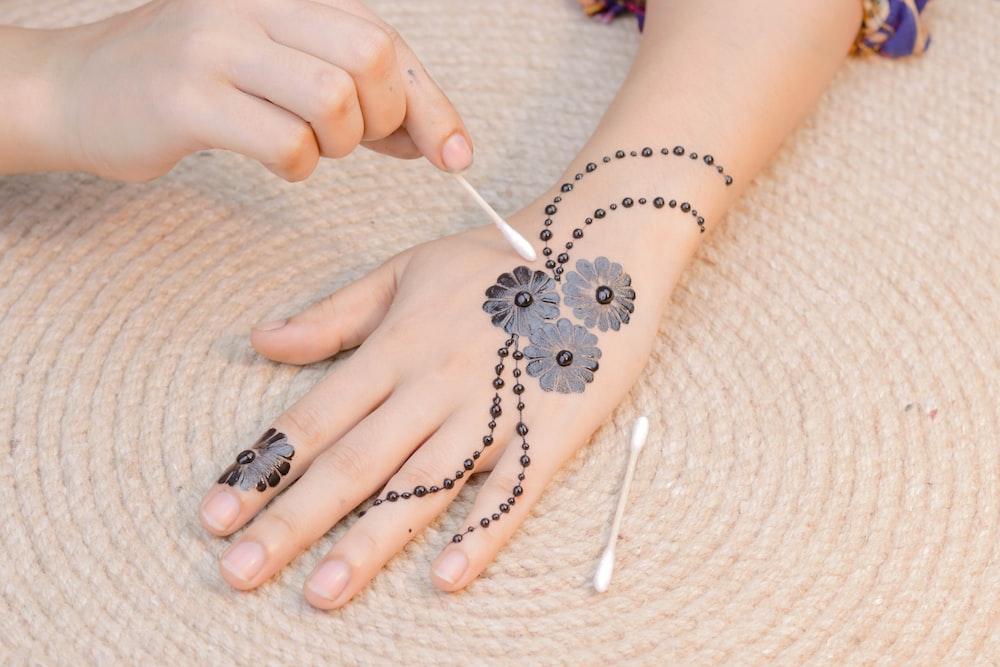 black flower hand tattoo