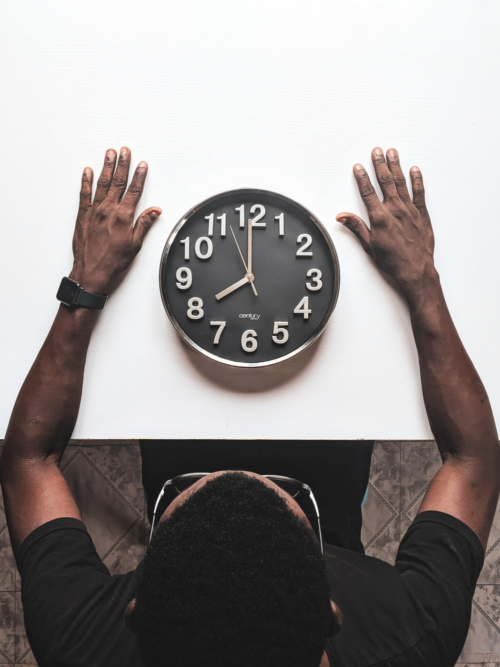 round black and white analog wall clock in front of man