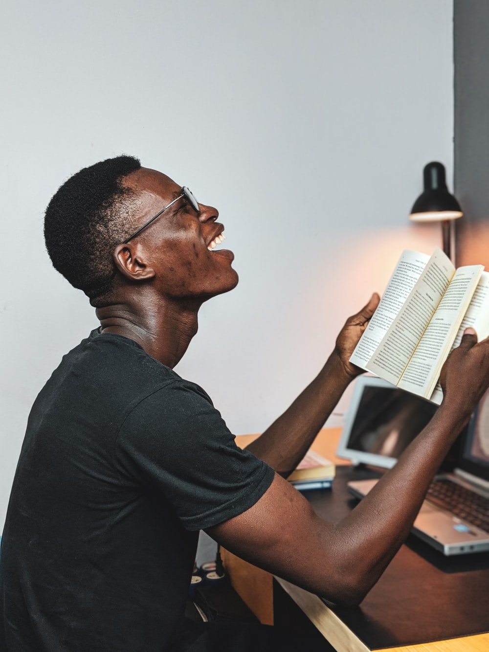man reads book and smiles