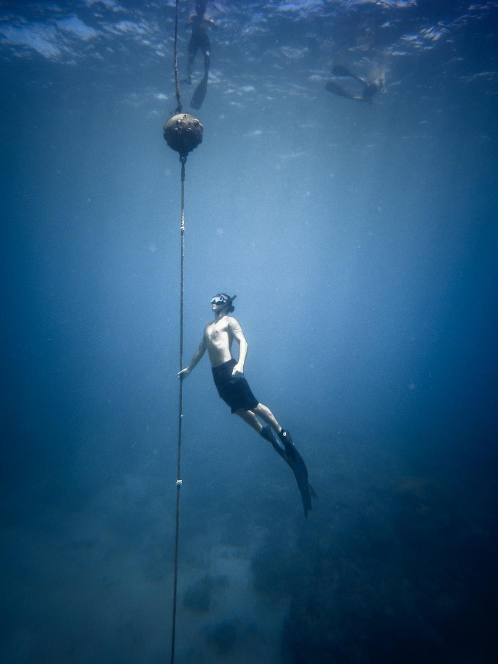 man wearing snorkeling gear swimming underwater