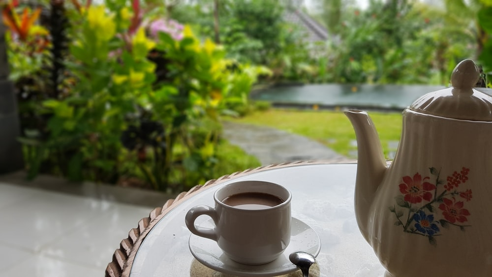 coffee in white ceramic teacup near white and multicolored teapot on round table